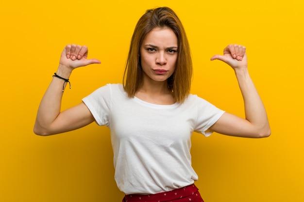 若い自然な白人女性は、誇りを持って自信を持って感じます。