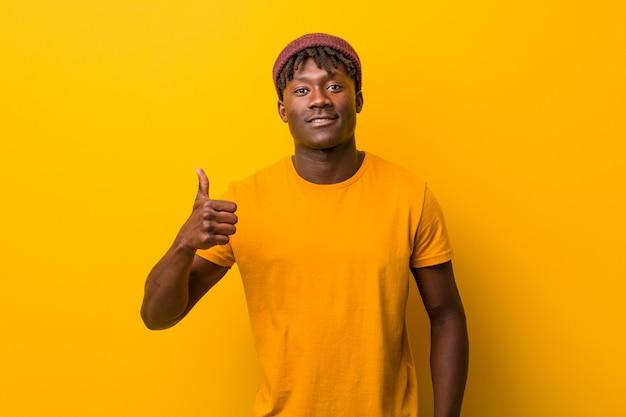 笑みを浮かべて、親指を上げる黄色の背景の上にラスタを着ている若い黒人男性