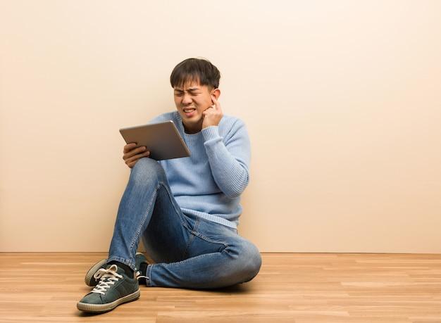 Молодой китайский человек, сидящий с помощью своего планшета, охватывающих уши руками