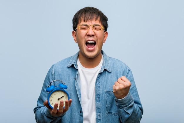 Молодой китайский мужчина держит будильник удивлен и шокирован
