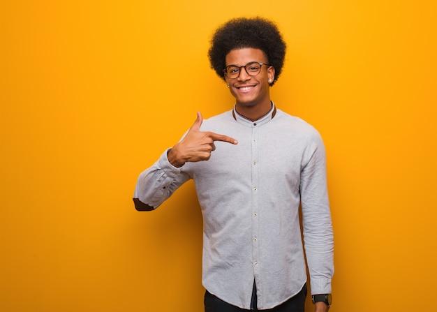 自信を持って、自信を持ってシャツコピースペースを手で指しているオレンジ色の壁人の上の若いアフリカ系アメリカ人男性