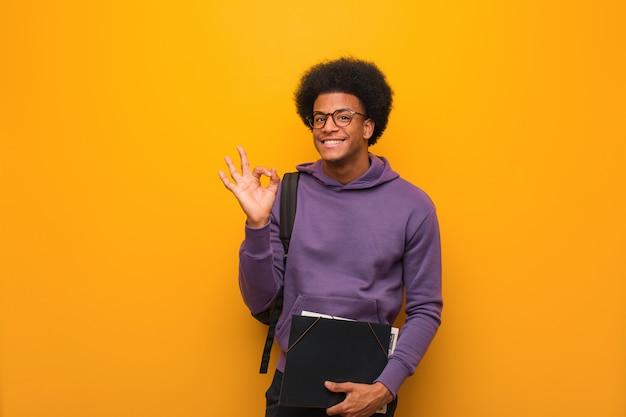 Молодой студент афроамериканца жизнерадостный и уверенно делает хорошо жест