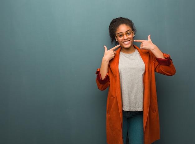 口を指している青い目の笑顔で若い黒人アフリカ系アメリカ人の女の子