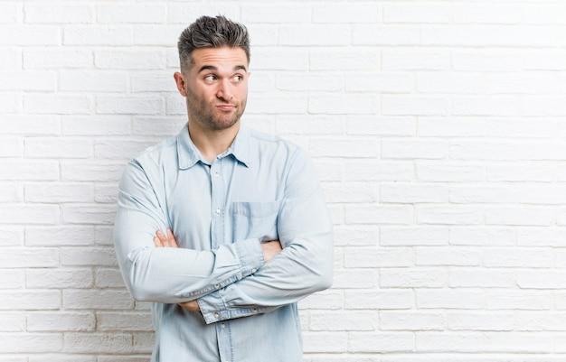 皮肉な表情でカメラで探している不幸なれんが造りの壁に対して若いハンサムな男。
