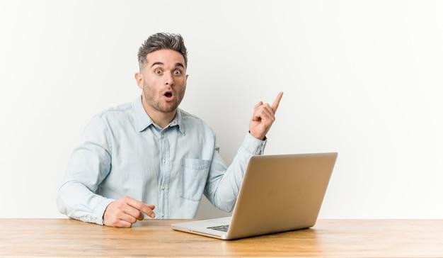 Молодой красивый человек, работающий с его ноутбуком, указывая в сторону