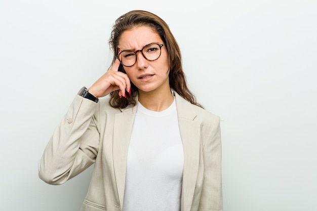 人差し指で失望のジェスチャーを示す若いヨーロッパのビジネス女性。