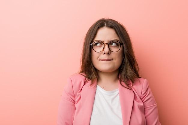 若いプラスサイズのビジネス白人女性は混乱し、疑わしく不確実な気がします。