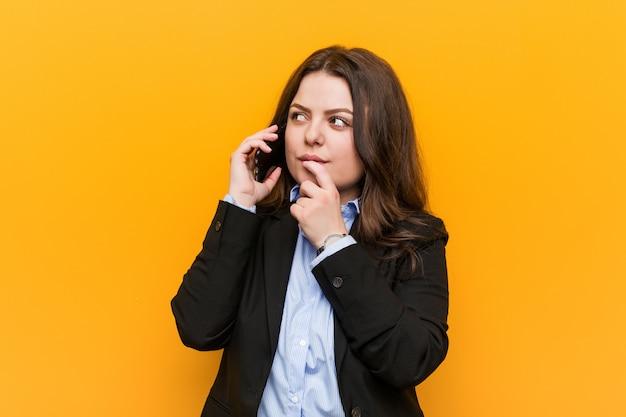 疑わしいと懐疑的な表現で横に探している携帯電話を保持している若い曲線プラスサイズビジネス女性。