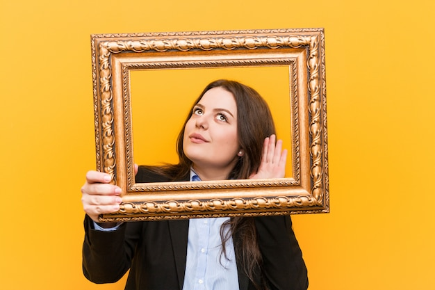 ゴシップを聞いてしようとしているフレームを保持している若い曲線プラスサイズビジネス女性。