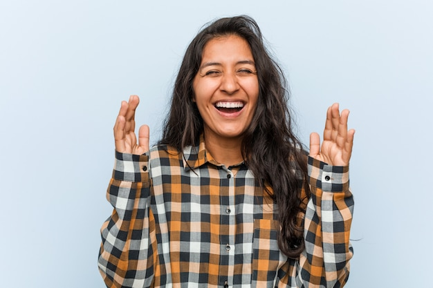 たくさん笑ってうれしそうな若いクールなインドの女性。幸福の概念