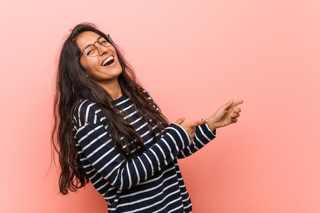 知的なインドの若い女性が離れて人差し指で指して興奮しています。