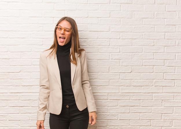 若いかなりビジネス起業家女性ウインク、おかしい、フレンドリーでのんきなジェスチャー
