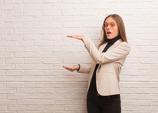 非常に驚いてショックを受けて何かを保持している若いかなりビジネス起業家の女性
