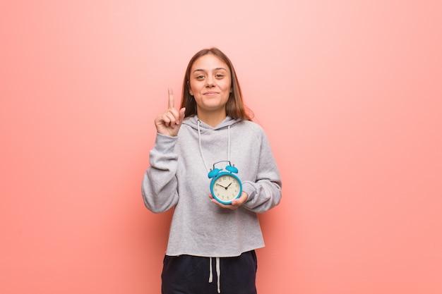 Молодая милая кавказская женщина показывая номер один. она держит будильник.