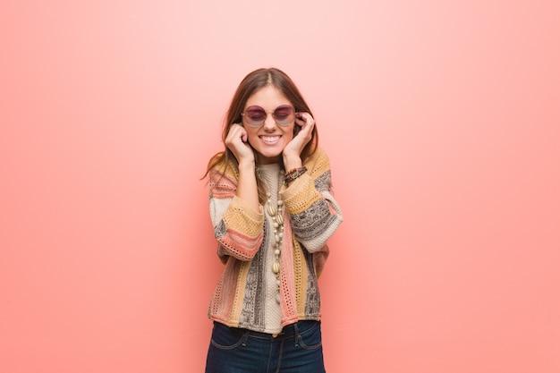 Молодая хиппи женщина на розовом покрытии ушей руками