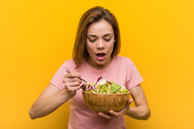 新鮮でおいしいサラダを食べるビーガン若い女性。