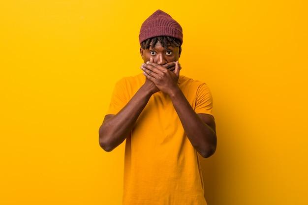 黄色の背景の上にラスタを着ている若い黒人男性が手で口を覆っているショックを受けた。