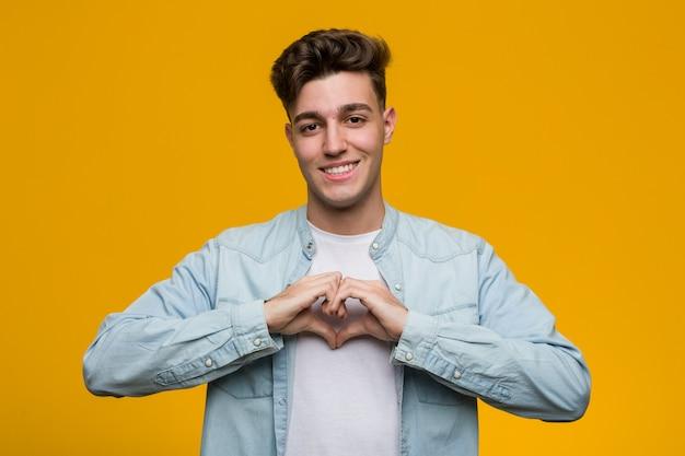Молодой красивый студент носить джинсовые рубашки, улыбаясь и показывая форму сердца с его руки.