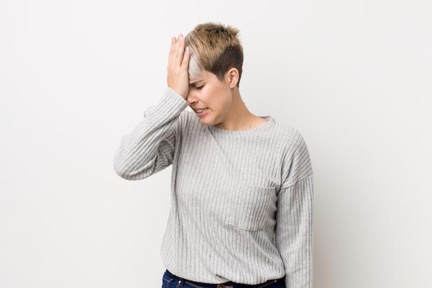 曲線を白人の若い女性は何かを忘れて、手のひらで額をたたくと目を閉じて白で隔離されます。