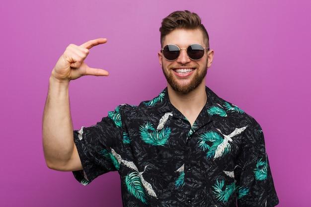 休暇を身に着けている若い男は、人差し指で少し何かを持って、笑顔で自信を持って見てください。