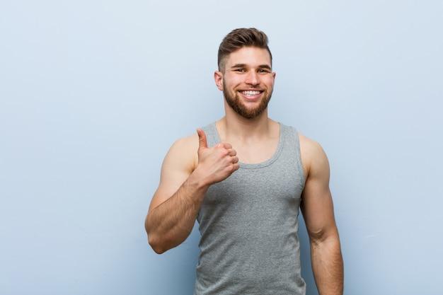 Молодой красавец фитнес, улыбаясь и поднимая большой палец вверх