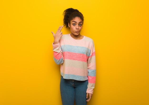自殺ジェスチャーをしている青い目を持つ若い黒アフリカ系アメリカ人の女の子