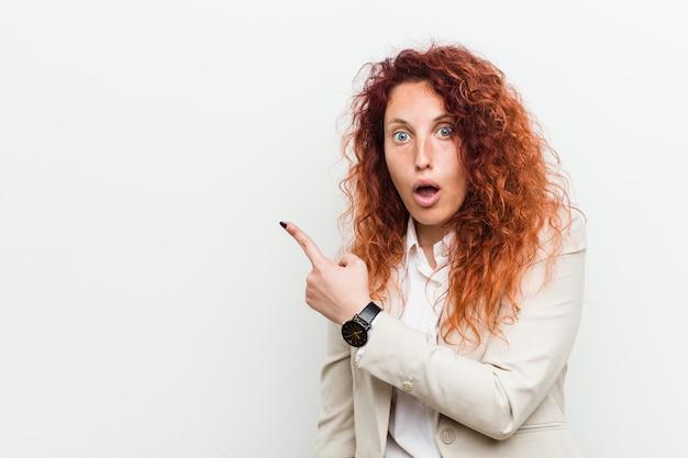 側を指している白い背景に対して隔離される若い自然な赤毛ビジネス女性