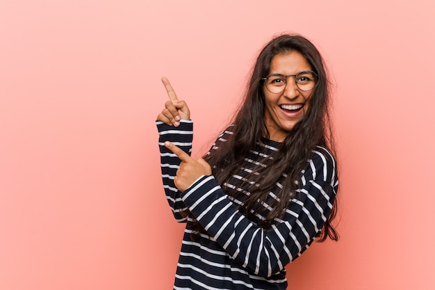 興奮と欲求を表現するコピースペースを人差し指で指している若い知的インド人女性。