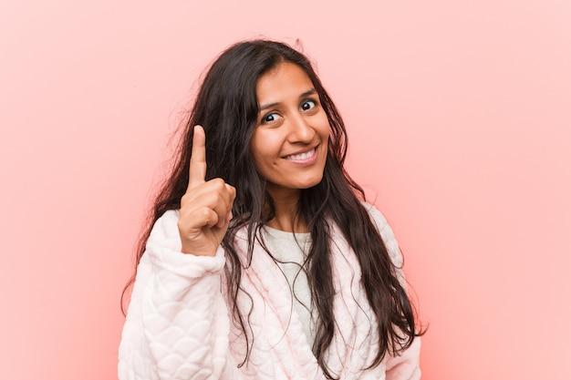 アイデア、インスピレーションの概念を持つパジャマを着ている若いインド人女性。