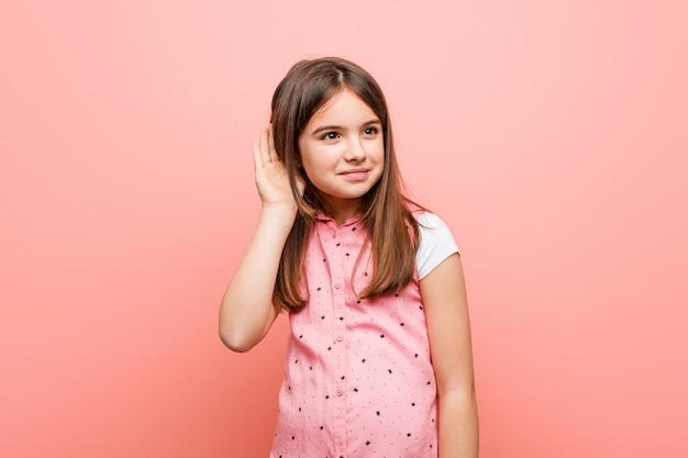 ゴシップを聞こうとしているかわいい女の子。