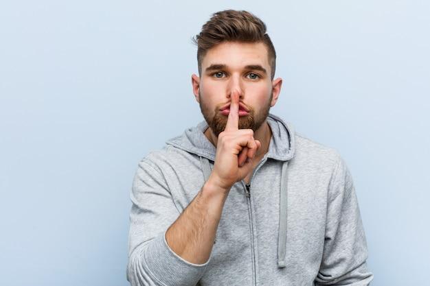 秘密を守るか沈黙を求める若いハンサムなフィットネス男。