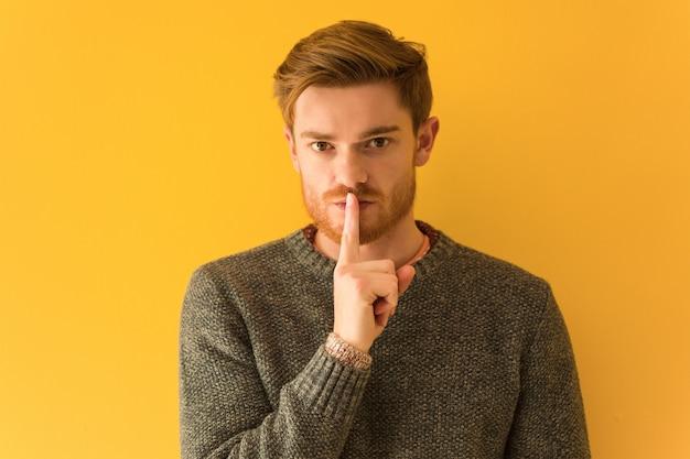 赤毛の若い男の顔のクローズアップ、秘密を守る、または沈黙を求める