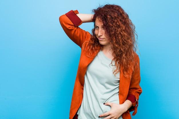 若い赤毛のエレガントな女性の頭の後ろに触れて、考えて、選択をします。