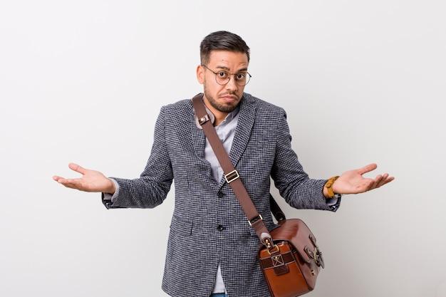 疑いとジェスチャーで肩をすくめて白い壁に対して若いビジネスフィリピン人男性。