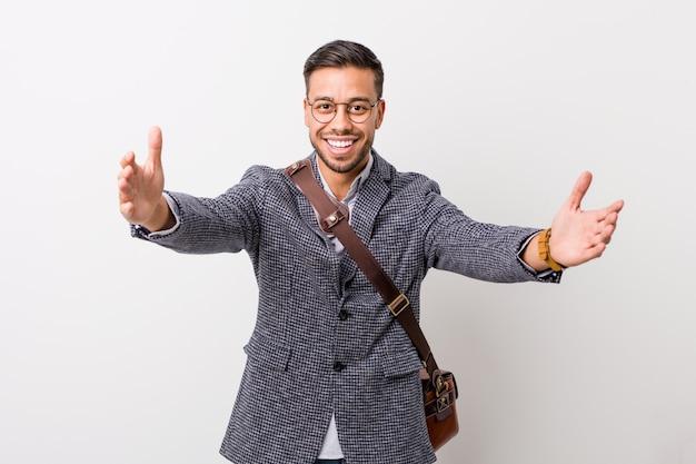 白い壁に対して若いビジネスフィリピン人男性は、カメラに抱擁を与えることを確信しています。
