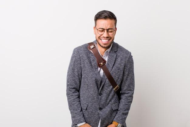 Молодой деловой филиппинский мужчина на фоне белой стены смеется и закрывает глаза, чувствует себя расслабленным и счастливым.