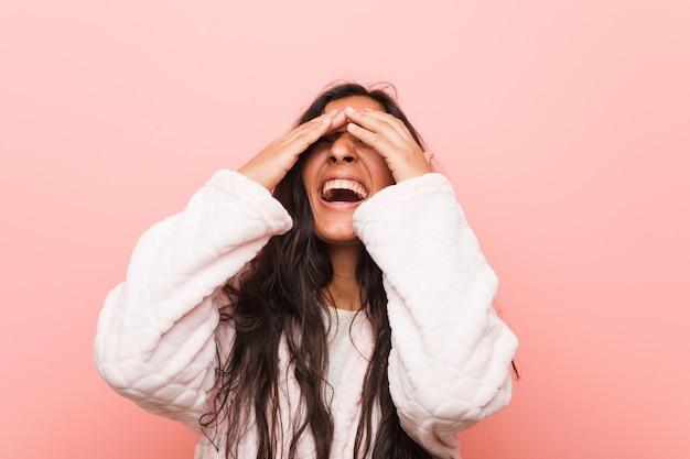 パジャマを着ている若いインド人女性は手で目を覆っています、驚きを広く待っている笑顔。