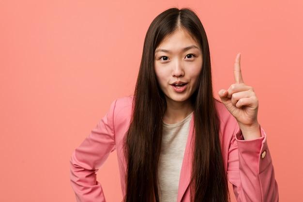 アイデア、インスピレーションの概念を持つピンクのスーツを着ている若いビジネス中国女性。