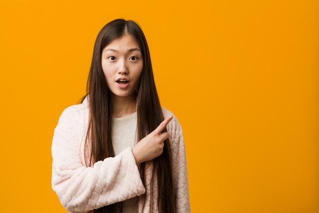 側を指しているパジャマの若い中国人女性