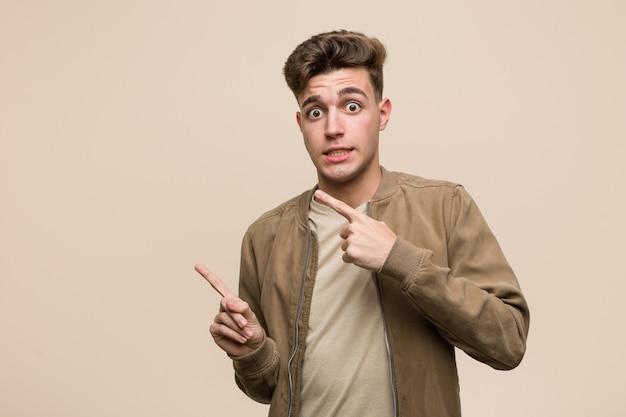 茶色のジャケットを着た若い白人男性がコピースペースに人差し指で指しているショックを受けた。