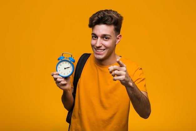 目覚まし時計を持って若い学生男が正面に興奮しています。
