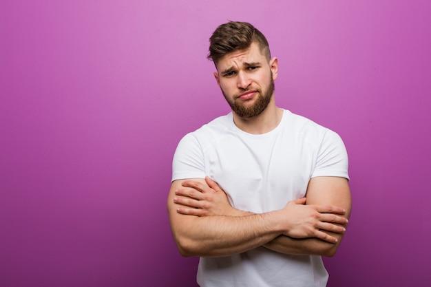 皮肉な表情でカメラに探している不幸な若いハンサムな白人男性。
