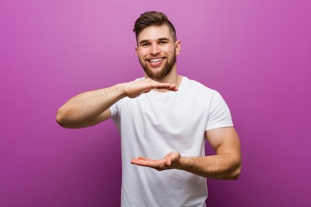 両手で何か、製品のプレゼンテーションを持って若いハンサムな白人男性。