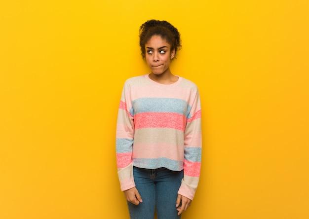アイデアを考えて青い目を持つ若い黒アフリカ系アメリカ人の女の子