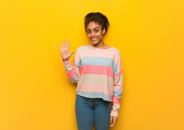 Молодая черная афроамериканская девушка с голубыми глазами показывает номер пять