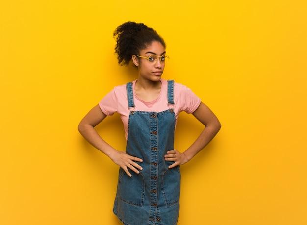 非常に怒っている誰かを叱る青い目を持つ若い黒アフリカ系アメリカ人の女の子
