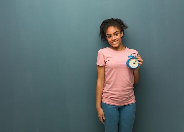 大きな笑顔で陽気な若い黒人女性。彼女は目覚まし時計を持っています。