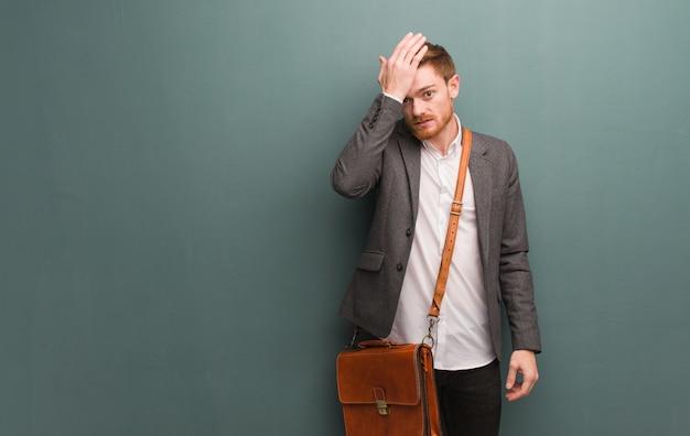 若い赤毛のビジネスマンの心配と圧倒