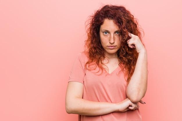 指で寺院を指して、考えて、タスクに焦点を当てた、自然で本格的な赤毛の若い女性。