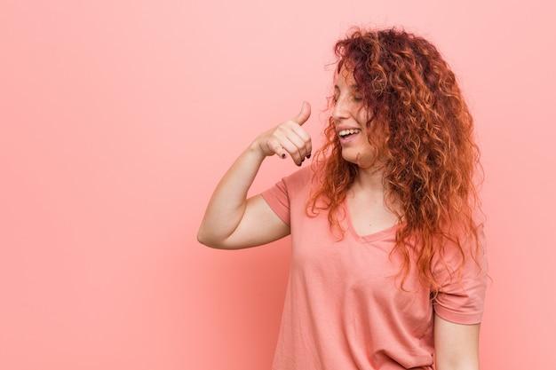携帯電話を示す自然で本格的な赤毛の女性が指でジェスチャーを呼び出します。